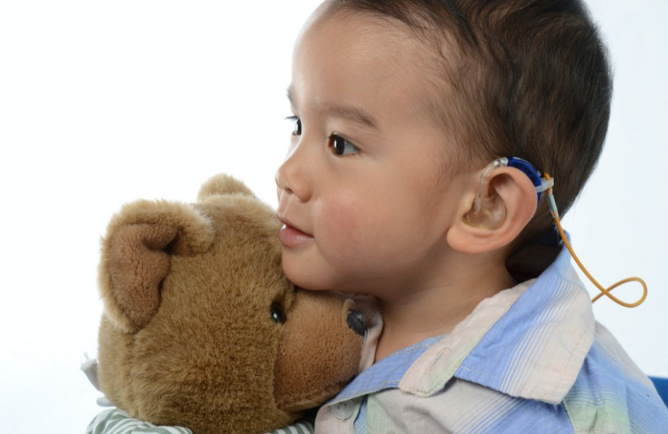 A child with a cochlear implant, holding a teddy bear