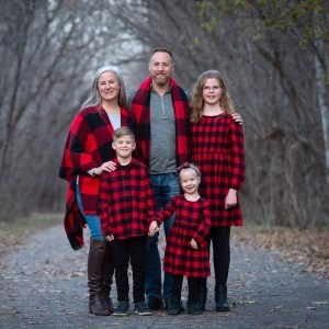 Dawson family wearing matching plaid and surrounded by trees