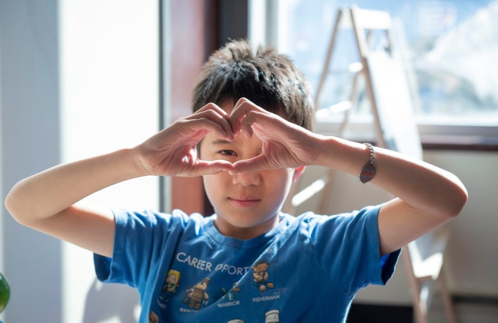 Young boy with heart hands