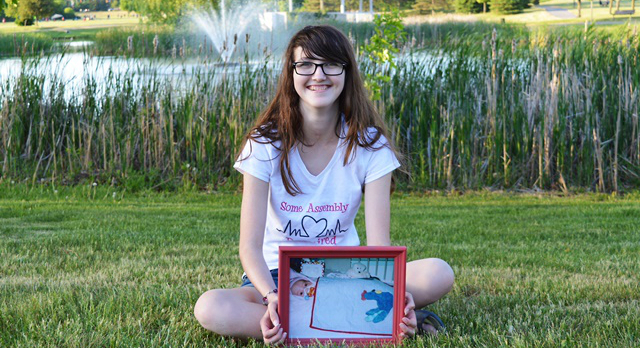 A teenage Abby MacMillan holds a picture of herself in the NICU