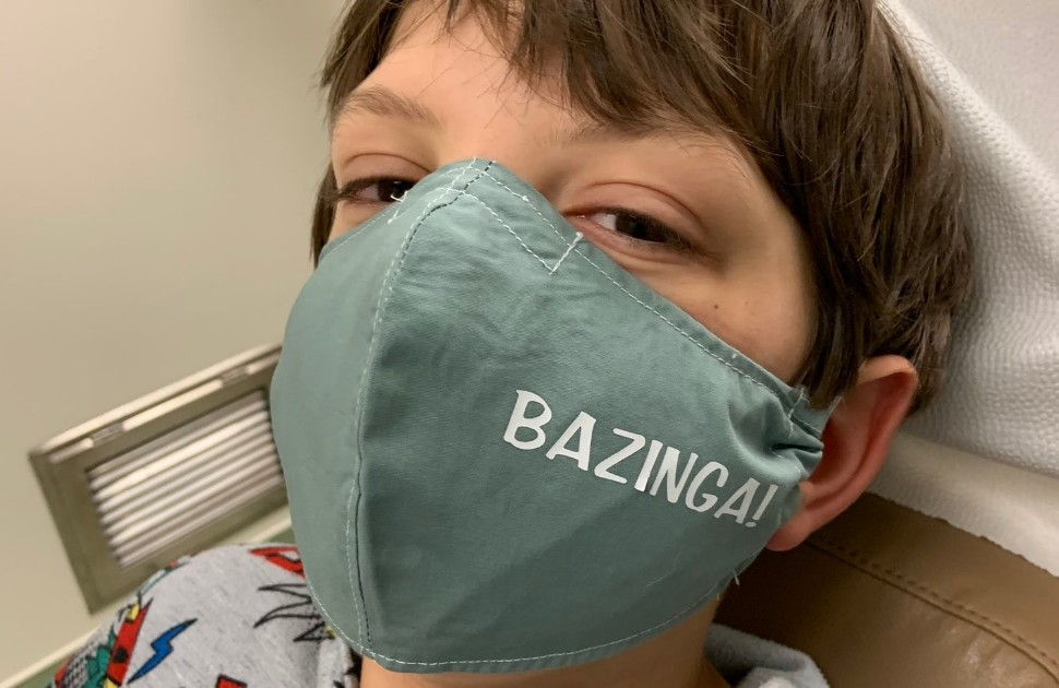 "Young boy wearing a cloth mask that says ""Bazinga"" on it"