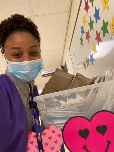 CHEO Volunteer in purple vest and face mask