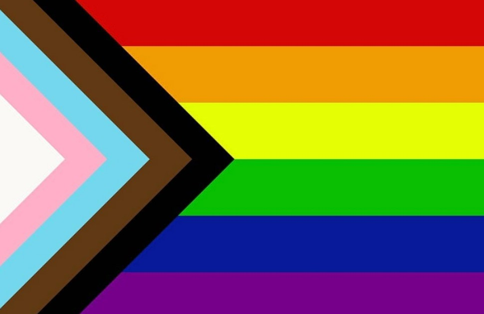 Progress pride flag, with horizontal red, orange, yellow, green, blue and purple stripes and a chevron shape on the left side with white, pink and blue stripes