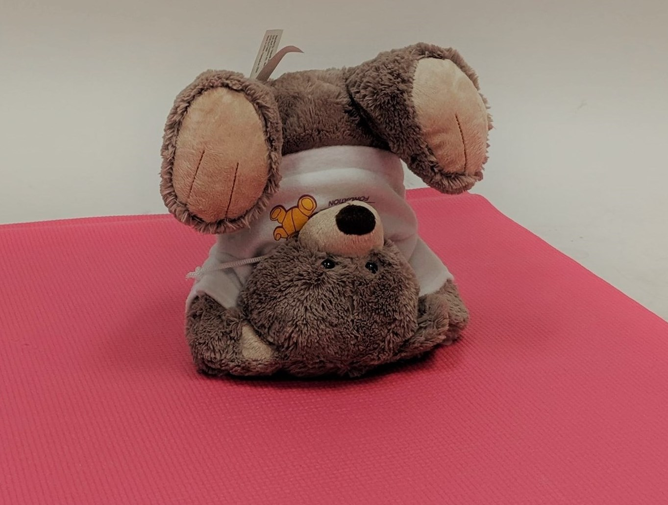 CHEO bear doing a headstand on a yoga mat
