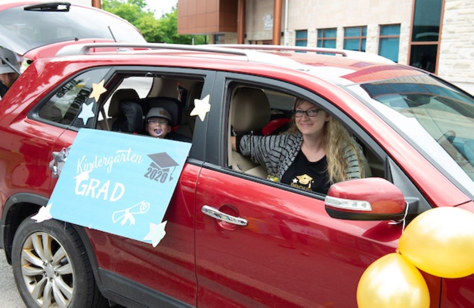 Little boy and mom in a car displaying a graduation sign