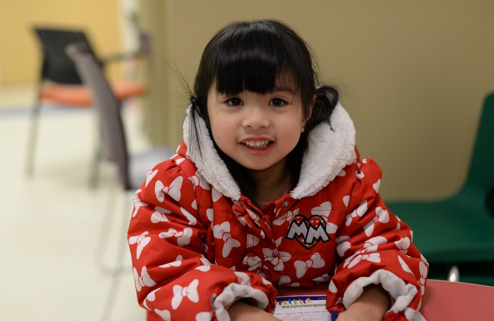 A young girl in a winter coat, smiling at the camera